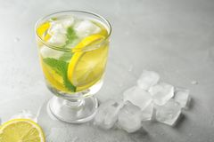Glass with lemon water and ice cubes. On table royalty free stock photos