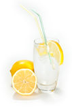 Glass with lemonade. A glass filled up with lemonade and ice isolated on a white background royalty free stock images