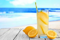 Glass of lemonade against a vibrant blue ocean background. Glass of lemonade with straw on white wood against a vibrant blue ocean background Stock Image