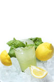 Glass of lemonade with basil leaves, lemons and ice cubes isolated on white Stock Photo