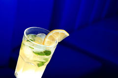 Glass of lemonade with the slice of lemon and mint. Blurred background Royalty Free Stock Images