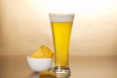 Glass of light amber beer and bowl with chips Stock Images