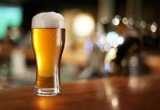 Glass of light beer. Glass of light beer on a dark pub Royalty Free Stock Image