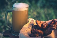 Glass of light beer against background of green trees outdoor. Snack sausage, smoked chicken wings, vintage toning picture. Glass of light beer against royalty free stock photography