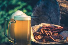 Glass of light beer against background of green trees outdoor. Snack sausage, smoked chicken wings, vintage toning picture. Glass of light beer against Royalty Free Stock Images