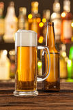 Glass of light beer with bar on background Stock Photos