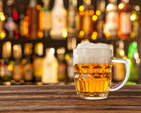 Glass of light beer with bar on background Royalty Free Stock Photos