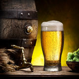 Glass of light beer and barrel. Glass of light beer and barrel on the wooden table stock photo