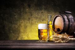 Glass of light beer with bottle and barrel Stock Photo