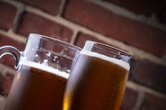 Glass of light beer on a dark pub. Background with Glass of light beer on a dark pub royalty free stock image