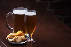 Glass of light beer on a dark pub. Royalty Free Stock Images