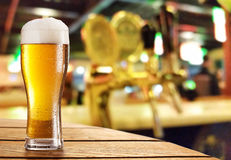 Glass of light beer on a dark pub. Glass of light beer on a dark pub desk Stock Photo