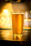 Glass of light beer on a dark pub. Stock Images