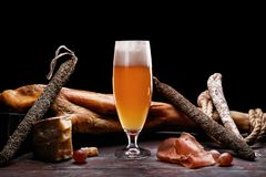 A glass of light beer foam, leg, Parma ham, expensive varieties of sausage and cheese with mold. On black background. Place for logo royalty free stock images