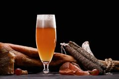 A glass of light beer foam, leg, Parma ham, expensive varieties of sausage and cheese with mold. stock photos
