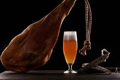 A glass of light beer foam, leg, Parma ham, expensive varieties of sausage. On black background. Place for logo royalty free stock photography