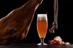 A glass of light beer foam, leg, Parma ham. stock image