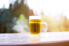 Glass of light beer with foam on a wooden table. Garden party. Natural background. Alcohol. Draft beer. Stock Photo
