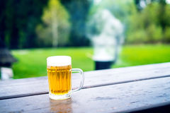 Glass of light beer with foam on a wooden table. Garden party. Natural background. Alcohol. Draft beer. Royalty Free Stock Photo