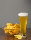 Glass of light beer and the golden chips Stock Photo