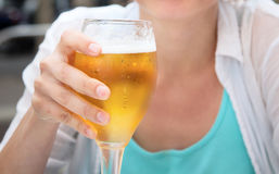 Glass of light beer in  hand Stock Photos