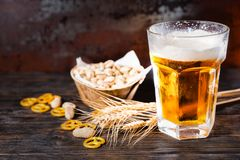 Glass with light beer and a head of foam near plate with pistach. Ios, wheat, scattered small pretzels and peanuts on dark desk. Food and beverages concept Stock Photography