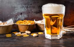 Glass with light beer and a head of foam, plates with pistachios. Small pretzels and peanuts on background. Food and beverages concept Royalty Free Stock Image