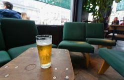 Glass of light beer inside bar or cafe with drinking people, old chairs and other vintage furniture. Glass of light beer inside bar or cafe with drinking people Stock Image