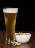 Glass of light beer and pistachio in a bowl Royalty Free Stock Images