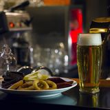 The glass of light beer and plate of snacks on the bar. The glass of light beer and a plate of snacks on the bar counter Royalty Free Stock Photo