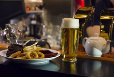 The glass of light beer and a plate of snacks on the bar. The mug of light beer and the plate of snacks on the bar counter Royalty Free Stock Photo