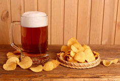 Glass of light beer and potato chips Stock Photography