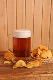 Glass of light beer and potato chips Royalty Free Stock Photos