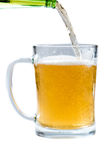 Glass of light beer pouring from bottle on a white background Royalty Free Stock Images