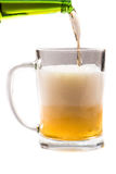 Glass of light beer pouring from bottle on a white background Royalty Free Stock Image