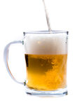 Glass of light beer pouring from bottle on a white background Royalty Free Stock Photography