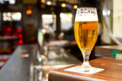 Glass of light beer on a pub. A Glass of light beer on a pub royalty free stock images