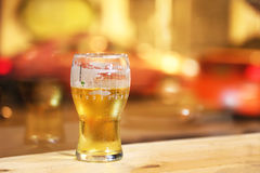 Glass of light beer reflects city streets. Royalty Free Stock Photography