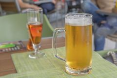 Glass of light beer on a restaurant table royalty free stock photography