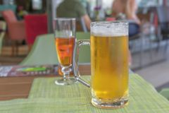 Glass of light beer on a restaurant table close royalty free stock photography