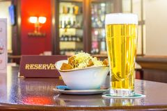 A glass of light beer with rusks cheese, a tablet - is reserved on a wooden table in the restaurant bar. A glass of light beer with rusks cheese, a tablet - is Royalty Free Stock Image