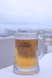 Glass of light beer on the table in outside cafe, Bali island, Indonesia. royalty free stock photos