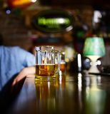 Glass of light beer on wooden bar counter. Man sits behind glass of light beer. Service and alcohol concept. Glass of draft beer on blurred bar background Royalty Free Stock Photo