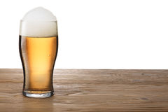 Glass of light beer on wooden table. Moist glass of light beer with foam on either wooden table or bar counter. Clipping pahts for both glass and background royalty free stock photography