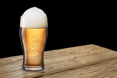Glass of light beer on wooden table. Moist glass of light, frothy beer with foam on either wooden table or bar counter. Clipping pahts for both glass and stock photo