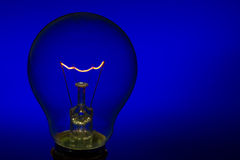 Glass light bulb with burning filament upright with blue backgro. Glass light bulb with burning filament upright with bright blue background Royalty Free Stock Images