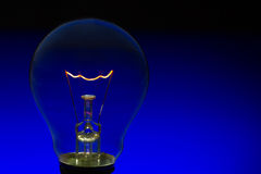 Glass light bulb with burning filament upright with blue backgro Royalty Free Stock Photos