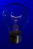 Glass light bulb with burning filament upright. With bright blue background Stock Photography