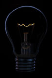 Glass light bulb with burning filament upright. With dark background Stock Photo