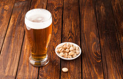glass of light cold frothy beer, nuts old wooden table Royalty Free Stock Photo